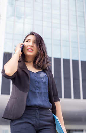 confidence smart asian business lady hold her laptop and talking front of high building in urban location action serious