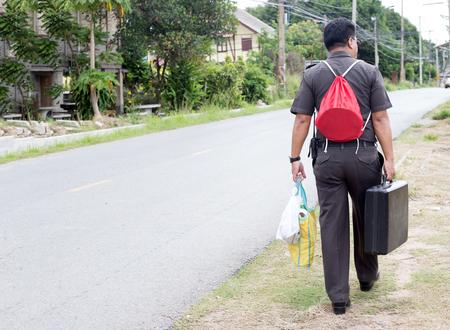 back of governor man Thai uniform walk back to rural home Фото со стока