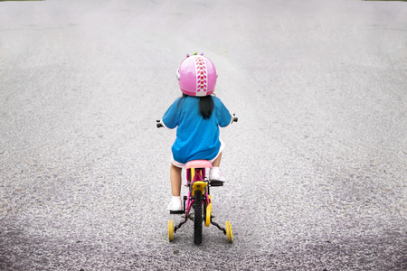 little girl riding bycicle to adventure on the street background Stock Photo