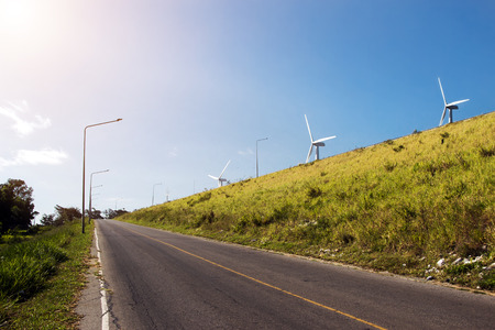 road to wind turbine on blue sky and mountain for background Stock Photo