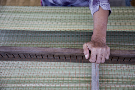 asian hand use wood plate to lock string for made rattan mat in Thailand handmade product Standard-Bild