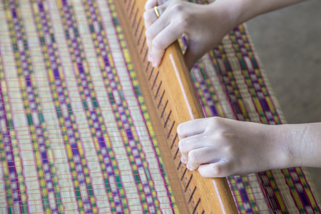 asian hand use wood plate to lock string for made rattan mat in Thailand handmade product Stock Photo