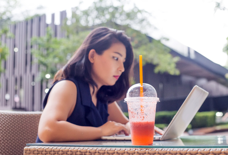 close up fruite punch and working woman do job with note book in concept work at home
