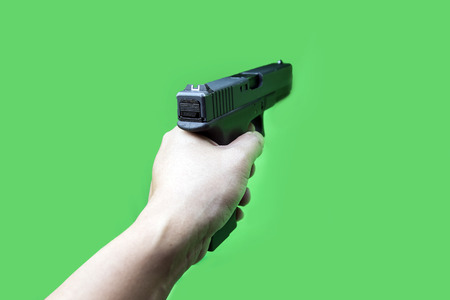 cloes up hand hold gun on green screen