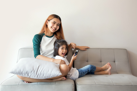 Asian kids using smartphone sitting together on sofa, happy little sister holding phone enjoying mobile app with smiling sister, cute children girl having fun playing mobile.Activities in digital generation concept.