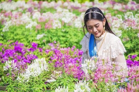 pretty Thai girl walk and watching flower in gardent with vintage Thai styl costume