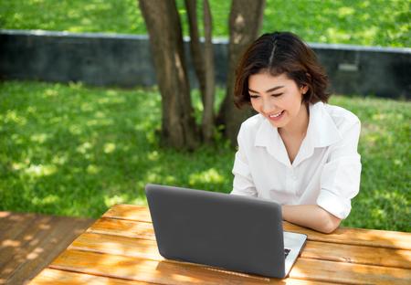 glückliches asiatisches Mädchen, das lacht und auf Laptop-Bildschirm auf Außenumgebung am Morgen zeigt. Verhalten der Menschen bei der Kommunikation oder beim Einkaufen im digitalen Konzept. Standard-Bild
