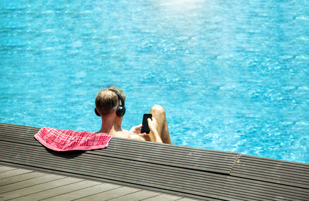 closse up head from backside with headphone relaxing near swimming pool. Man sun bath in summer and touch screen of mobile. Relax in vocation concept.