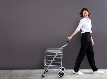 asian lady pull shopping cart with happy feeling. Shopaholic concept.