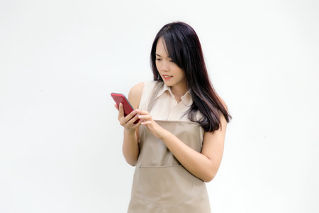 asian lady with apron dress look at mobile screen for learning about service online with application on white background
