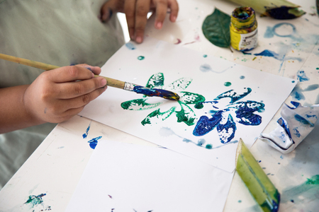 close up kid hand painting part plant and make art on paper with water color Stok Fotoğraf