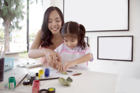 asian mother and daughter painting water color to make art object in creative activities.