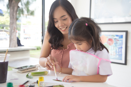 focus happy face of asian mother do painting with kids.