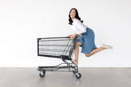 happy asian lady in shopping action with shopping cart on white background. Фото со стока