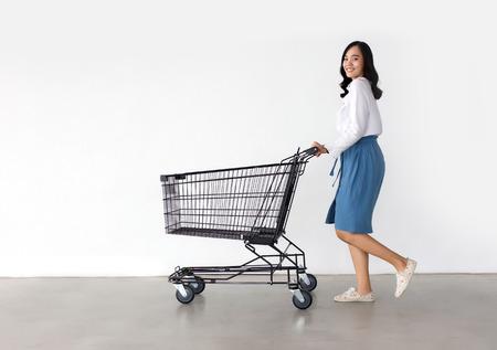 gelukkige Aziatische dame in winkelactie met winkelwagen op witte achtergrond.