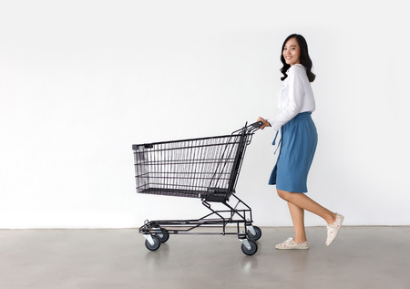 happy asian lady in shopping action with shopping cart on white background. 스톡 콘텐츠
