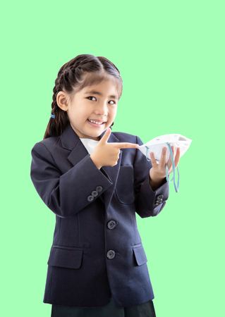 asian kids with air polution protect mask with student suite costume. Portrait action as block smoke smell on blue background (include clipping path)