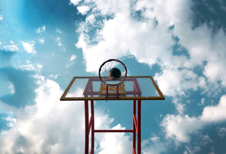 basketball play from bottom view with competition concept to catch ball on blue sky. outdoor sport on day light Фото со стока
