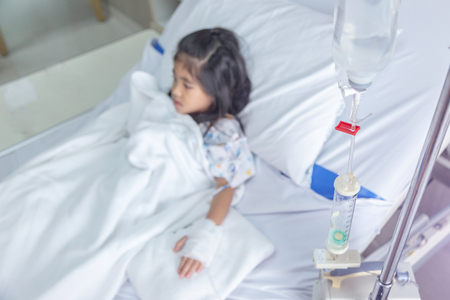 clinic heal kid Fluids Intravenous to blood vein in hosital room. Virus flue epidemic situation medicine healthy concept.(focus on red clip on tube of intravenous water)
