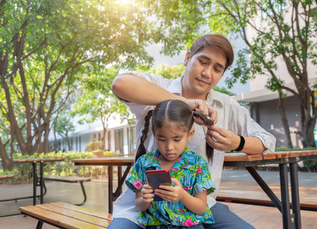 stepfather concept daddy love daughter do pigtail hair for kid at park in morning .Lovely moment of family. 版權商用圖片
