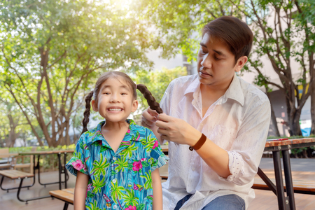 stepfather concept daddy love daughter do pigtail hair for kid at park in morning. Lovely moment of family together. Stock Photo