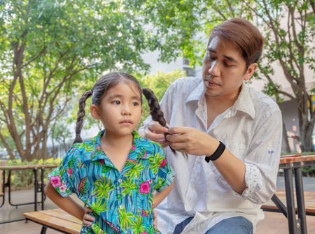 stepfather concept daddy love daughter do pigtail hair for kid at park in morning. Lovely moment of family.