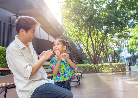 stepfather concept daddy love daughter do pigtail hair for kid at park in morning .Lovely moment of family. Stock Photo
