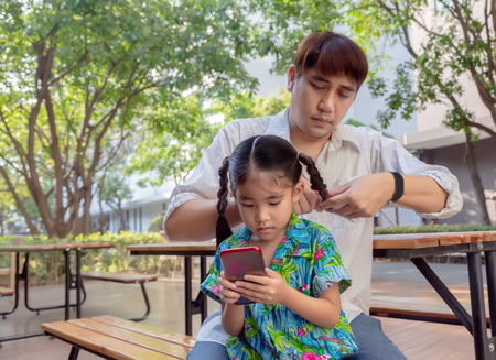 stepfather concept daddy love daugther do pigtail hair for kid with mobile at park in morning Lovely moment of family.