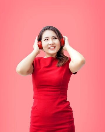 Red asian woman listen to music with headphones set and look up thinking action on red