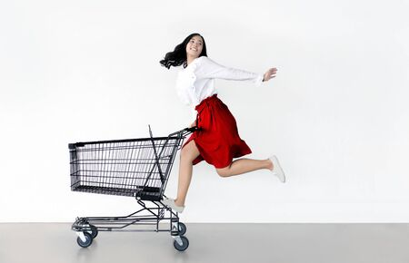 happy asian woman with shopping cart ready for shopping on sale season - Beautiful casual shopper girl going to the store. Reklamní fotografie