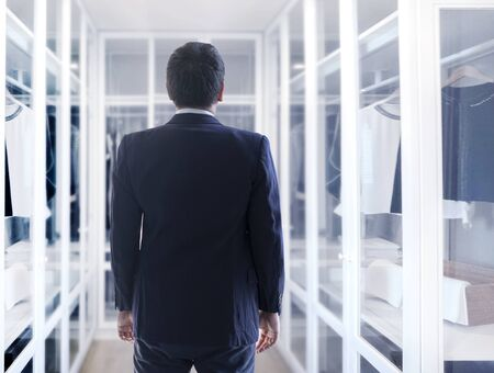 asian business man dress up with walk in clothes wardrobe in home designer concept Banque d'images