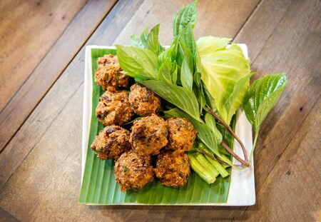 asian crispy Thai cusine call Larb Thod inside with herb and pork grill in ball. serve with vegetable