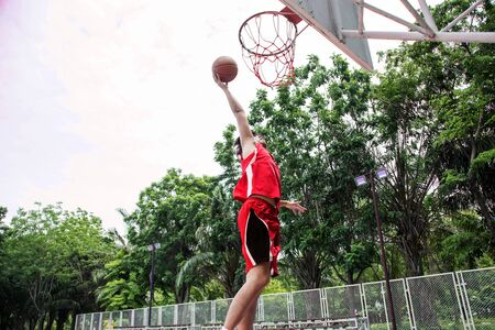 basketball player playing ball. Shooting to goal basket in green tree outdoor court