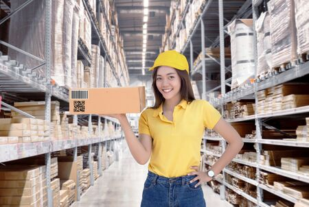Asian woman show paper box inventory from warehouse with smile.