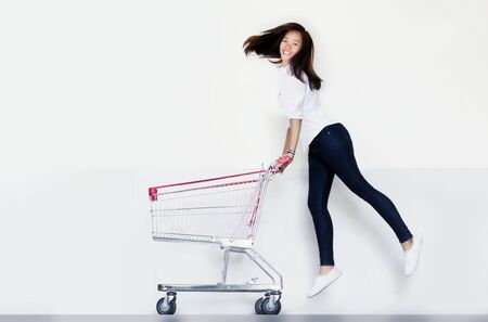 Happy asian woman love shopping action with shopping cart on white Reklamní fotografie