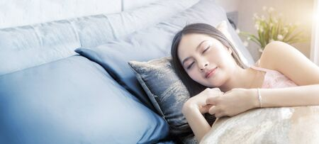 happy asian girl sleep with pillow on bed with morning light on bedroom, Banner size