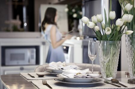 woman wife preparing romantic dinner for aniverary of love on table at home. (focus on flower and kitchenware on dinner table)