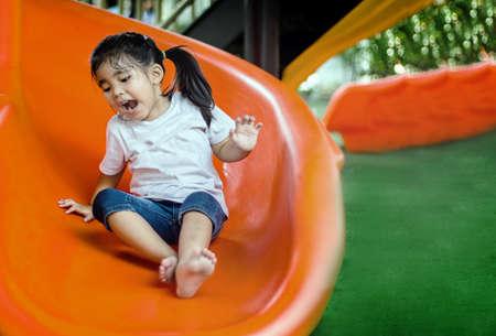 happy asian girl have fun with slider outdoor playpark Zdjęcie Seryjne