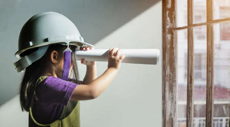 kids looking out to construction site near windows with engineer cap as builder in future job Zdjęcie Seryjne
