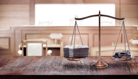 balancing of money and shackle on scales in courtroom with to magistrate in cour in the law of adjustment concept