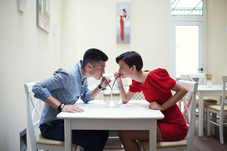 Romantic date in a restaurant. Beautiful couple. Handsome brunette guy in blue shirt and jeans with a girl in a red dress drinking coffee through a straw in a restaurant