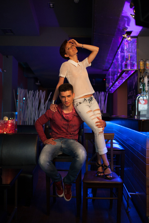 Romantic date in a restaurant. Beautiful couple. Handsome brunette guy with a girl in blue jeans and white blouse sitting in a bar Standard-Bild
