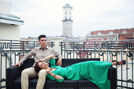 Souple relaxing on the terrace balcony with beautiful scenery on the ancient city. Brunette guy in a beige shirt and trousers sitting on the couch with a girl who lying him kneeling in a green dress.