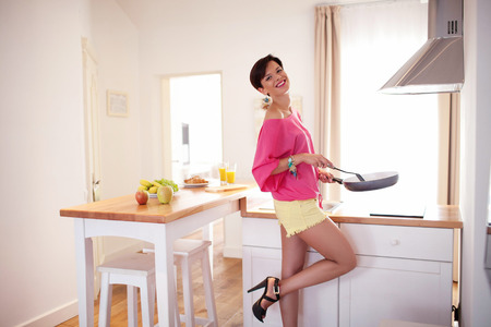 Beautiful girl prepare breakfast in a pink blouse and yellow shorts with a frying pan in the kitchen