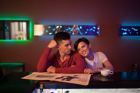 Romantic date in a restaurant. Beautiful couple. Handsome brunette guy with a girl in blue jeans and white blouse sitting in a bar and drink coffee and read the newspaper