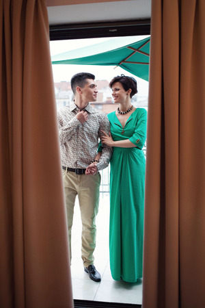 Romantic date on the balcony. Beautiful couple. Handsome brunette guy with a girl in a green dress.
