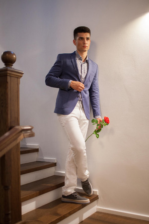 Handsome brunette guy in the purple jacket and white pants waiting for a girl on a ladder with a rose