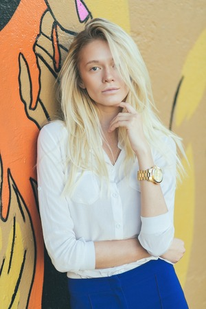 Attractive girl blonde with long hair in a white shirt and blue pants, against a wall with graffiti.
