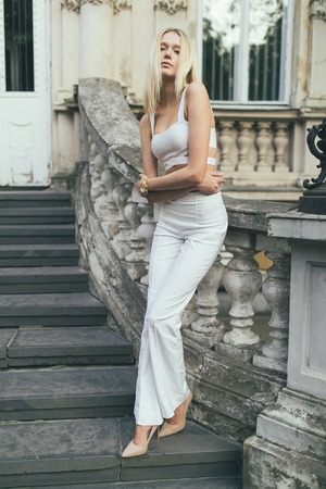 Attractive girl blonde with long hair, in white pants and a white top,standing against the backdrop of an old house architecture.