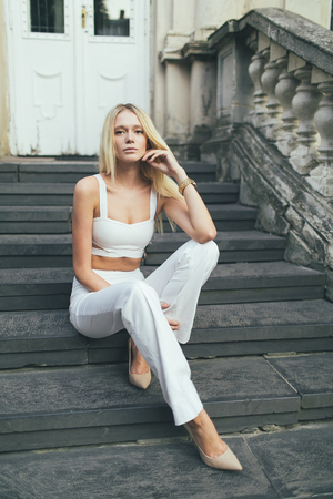Attractive girl blonde with long hair, in white pants and a white top, sitting on the stairs of an old house architecture.
